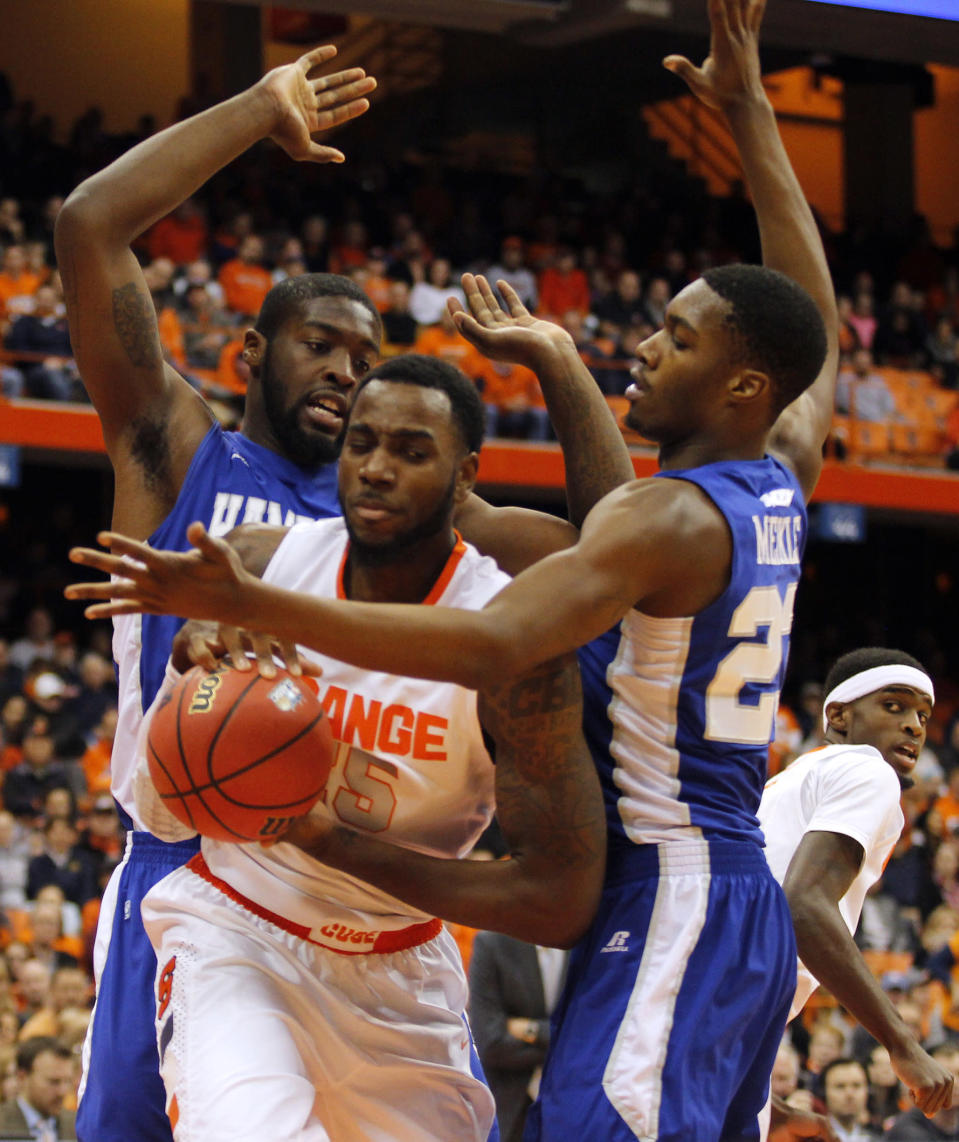 Syracuse's Rakeem Christmas, center, grabs a rebound under pressure by Hampton's Jervon Pressley, left, and Dwight Meikle, right, in the first half of an NCAA college basketball game in Syracuse, N.Y., Sunday, Nov. 16, 2014. (AP Photo/Nick Lisi)