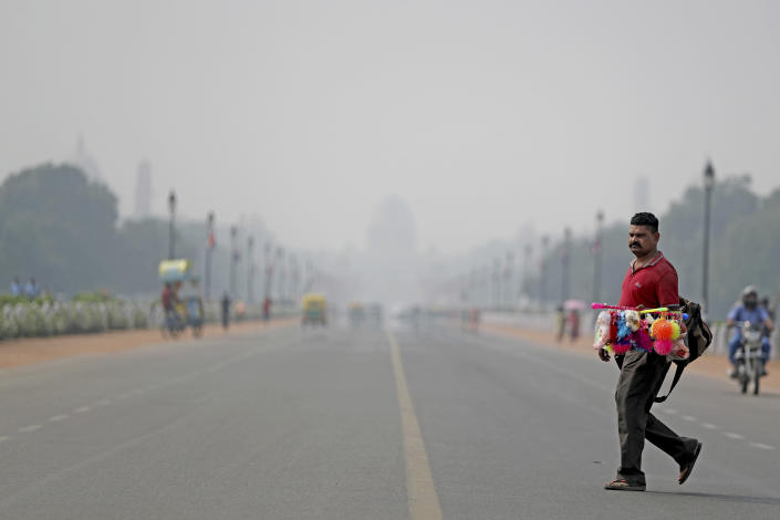 """India's Presidential Palace, in the backdrop, is covered with smog as as a roadside vendor crosses Rajapth, the ceremonial boulevard in New Delhi, India, Wednesday, Oct. 16, 2019. The Indian capital's air quality levels have plunged to """"poor,"""" a day after the government initiated stricter measures to fight chronic air pollution. The state-run Central Pollution Control Board's air quality index for New Delhi stood at 299 on Wednesday, about six times the recommended level. (AP Photo/Altaf Qadri)"""