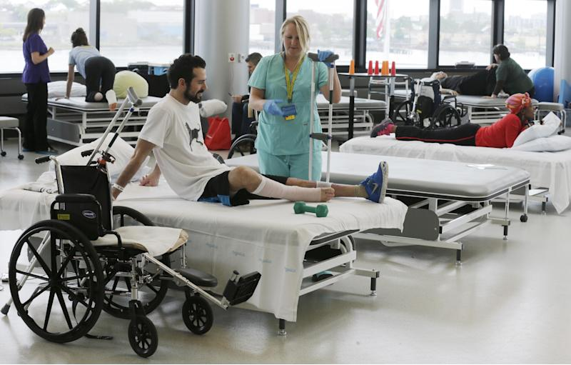 """In this Wednesday, May 22, 2013 photo, Boston Marathon bombing survivor Pete DiMartino, of Rochester, N.Y., talks with his physical therapist Julia Broyer during a session as other bombing survivors are treated at the Spaulding Rehabilitation Hospital in Boston. DiMartino was injured in an explosion near the finish line, which blew away much of one leg and burned the other. """"I don't want anybody feeling sorry for me,"""" he said. """"... I want people to see that this has made me a better person and I want people to become better people through what they see through me."""" (AP Photo/Charles Krupa)"""