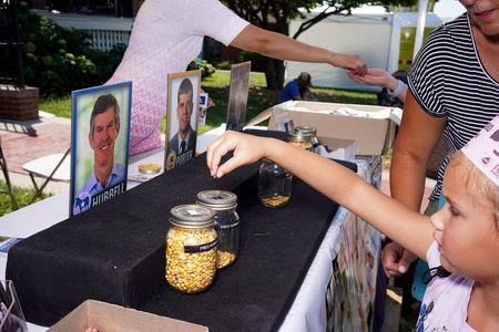 FILE PHOTO: Mazzie Ferchen, 6, of Urbandale casts a vote for Iowa gubernatorial candidate Fred Hubbell at a corn kernel voting station at the Iowa State Fair in Des Moines, Iowa, U.S., August 9, 2018. REUTERS/KC McGinnis/File Photo