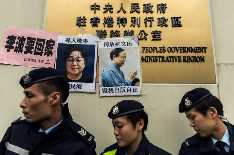 Police walk past missing person notices of Gui Minhai (L), one of five missing booksellers from the Mighty Current publishing house and Yau Wentian (R), a Hong Kong publisher jailed for 10 years over a book critical of Chinese President Xi Jinping