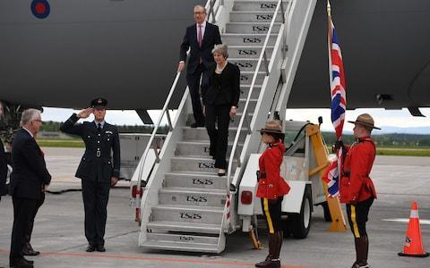 Prime Minister Theresa May and her husband Philip are greeted as they arrive at CAF Bagotville airfield - Credit: Getty