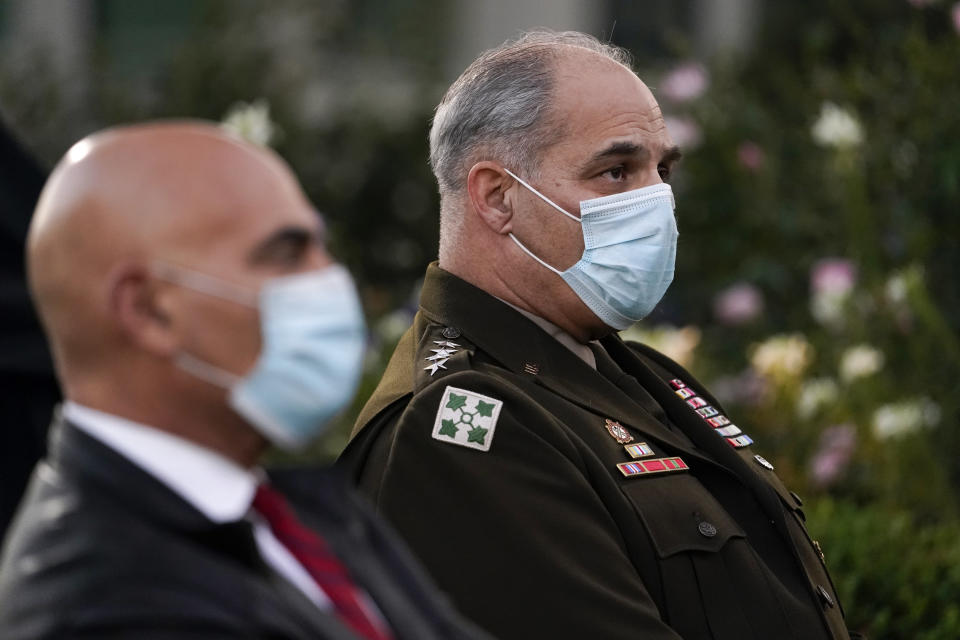 Army Gen. Gustave Perna, who is leading Operation Warp Speed, right, and Dr. Moncef Slaoui, chief adviser to Operation Warp Speed, listen during at an event in the Rose Garden of the White House, Friday, Nov. 13, 2020, in Washington. (AP Photo/Evan Vucci)