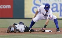Chicago White Sox Alejandro De Aza, left, dives back to base as Texas Rangers second baseman Ian Kinsler, right, attempts the tag in the first inning of a baseball game in Arlington, Texas, Wednesday, May 1, 2013. De Aza was safe on the play. (AP Photo/Brandon Wade)