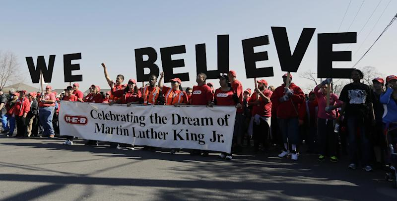 "Letters spelling ""We Believe"" are carried by a group during a march honoring Martin Luther King Jr., Monday, Jan. 20, 2014, in San Antonio. (AP Photo/Eric Gay)"