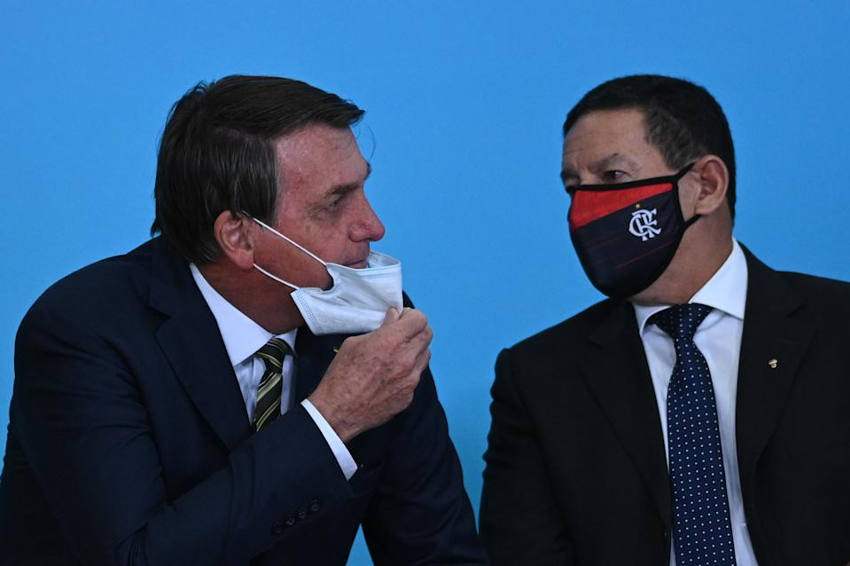 Jair Bolsonaro, Brazil's President removes his face mask to speak with Vice President Hamilton Mourao during the celebration ceremony of National Volunteer Day amid the coronavirus(COVID-19) pandemic at Planalto Palace in Brasilia, Brazil, on Aug. 28, 2020. (Photo by Andre Borges/NurPhoto via Getty Images)