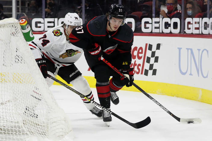 Carolina Hurricanes' Andrei Svechnikov (37) moves the puck against Chicago Blackhawks' Nicolas Beaudin (74) during the second period of an NHL hockey game in Raleigh, N.C., Monday, May 3, 2021. (AP Photo/Karl B DeBlaker)
