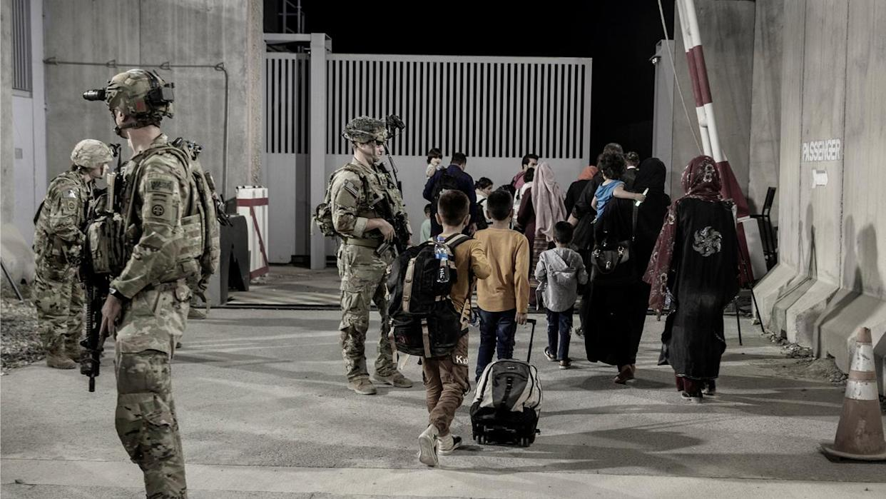 U.S. troops with the 82nd Airborne Division escort evacuees to buses at the airport in Kabul on Aug. 25, 2021.