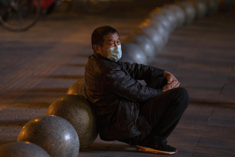 A man wearing a mask rests near barriers outside a shopping mall in Beijing on Friday, Oct. 30, 2020. China has managed to stem the spread of the coronavirus within the country even as the pandemic continues to surge globally. (AP Photo/Ng Han Guan)