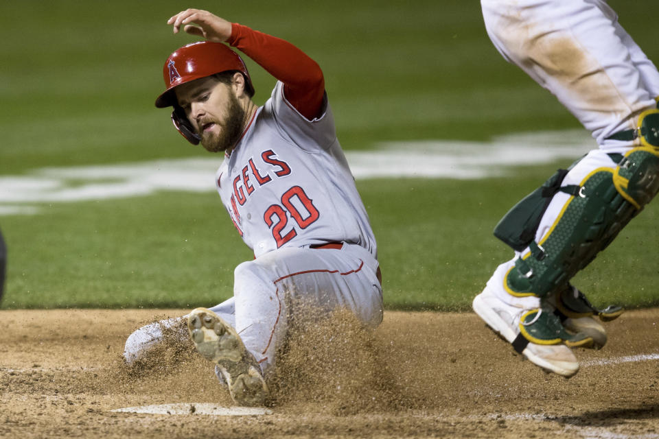 Los Angeles Angels' Jared Walsh (20) slides home to score against the Oakland Athletics during the seventh inning of a baseball game in Oakland, Calif., Monday, June 14, 2021. (AP Photo/John Hefti)