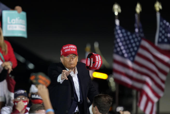President Donald Trump throws a hat to a supporter during a campaign rally at Des Moines International Airport, Wednesday, Oct. 14, 2020, in Des Moines, Iowa. (AP Photo/Charlie Neibergall)