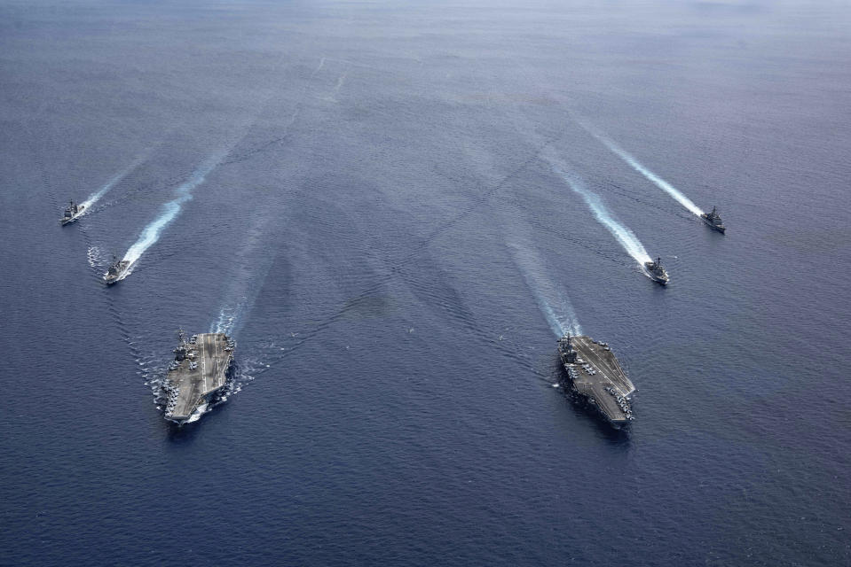 In this photo provided by U.S. Navy, the USS Ronald Reagan (CVN 76) and USS Nimitz (CVN 68) Carrier Strike Groups steam in formation, in the South China Sea, Monday, July 6, 2020. China on Monday, July 6, accused the U.S. of flexing its military muscles in the South China Sea by conducting joint exercises with two U.S. aircraft carrier groups in the strategic waterway.(Mass Communication Specialist 3rd Class Jason Tarleton/U.S. Navy via AP)