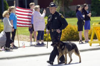 A K-9 officer leads a processional to the Holmes Convocational Center for the funeral services of Watauga County Sheriff's Deputies Sgt. Chris Ward and K-9 Deputy Logan Fox in Boone, N.C., Thursday, May 6, 2021. The two deputies were killed in the line of duty. (AP Photo/Gerry Broome)