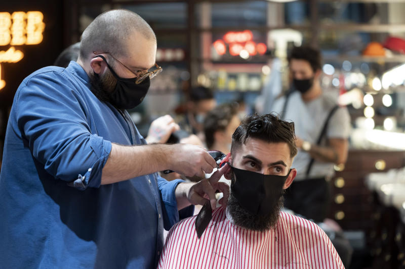 A member of the public has a haircut at a barbers in Manchester England, England, Saturday July 4, 2020. England is embarking on perhaps its biggest lockdown easing yet as pubs and restaurants have the right to reopen for the first time in more than three months. In addition to the reopening of much of the hospitality sector, couples can tie the knot once again, while many of those who have had enough of their lockdown hair can finally get a trim. (AP Photo/Jon Super)