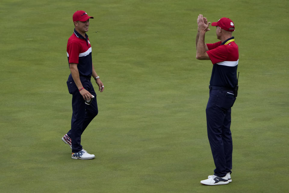 Team USA assistant captain Jim Furyk applauds Justin Thomas after the Ryder Cup matches at the Whistling Straits Golf Course Sunday, Sept. 26, 2021, in Sheboygan, Wis. (AP Photo/Jeff Roberson)