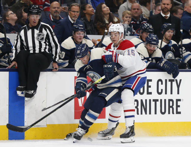 Columbus Blue Jackets' Riley Nash, left, takes the puck away from Montreal Canadiens' Jesperi Kotkaniemi, of Finland, during the first period of an NHL hockey game Tuesday, Nov. 19, 2019, in Columbus, Ohio. (AP Photo/Jay LaPrete)