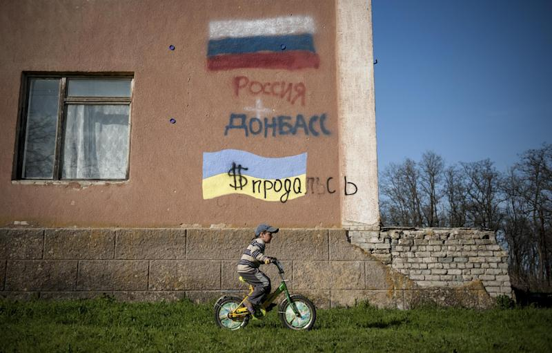 "A boy rides a bicycle past a building with Russian and Ukrainian national flags and words reading ""Ukraine had sold herself for dollars Russia"" in Uspenka village, 4 kilometers (2.8 miles) to the Ukrainian-Russian border, Donbas region, Ukraine, Friday, April 18, 2014. Dashing hopes of progress raised by a diplomatic deal in Geneva, pro-Russian insurgents who have occupied government buildings in more than 10 Ukrainian cities said Friday they will not leave them until the country's interim government resigns. (AP Photo/Evgeniy Maloletka)"