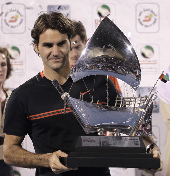 Roger Federer of Switzerland holds the winning trophy after defeating Andy Murray of Britain, rear centre, in the men's singles final at the Emirates Dubai ATP Tennis Championships in Dubai, United Arab Emirates, Saturday, March 3, 2012. (AP Photo/Hassan Ammar)