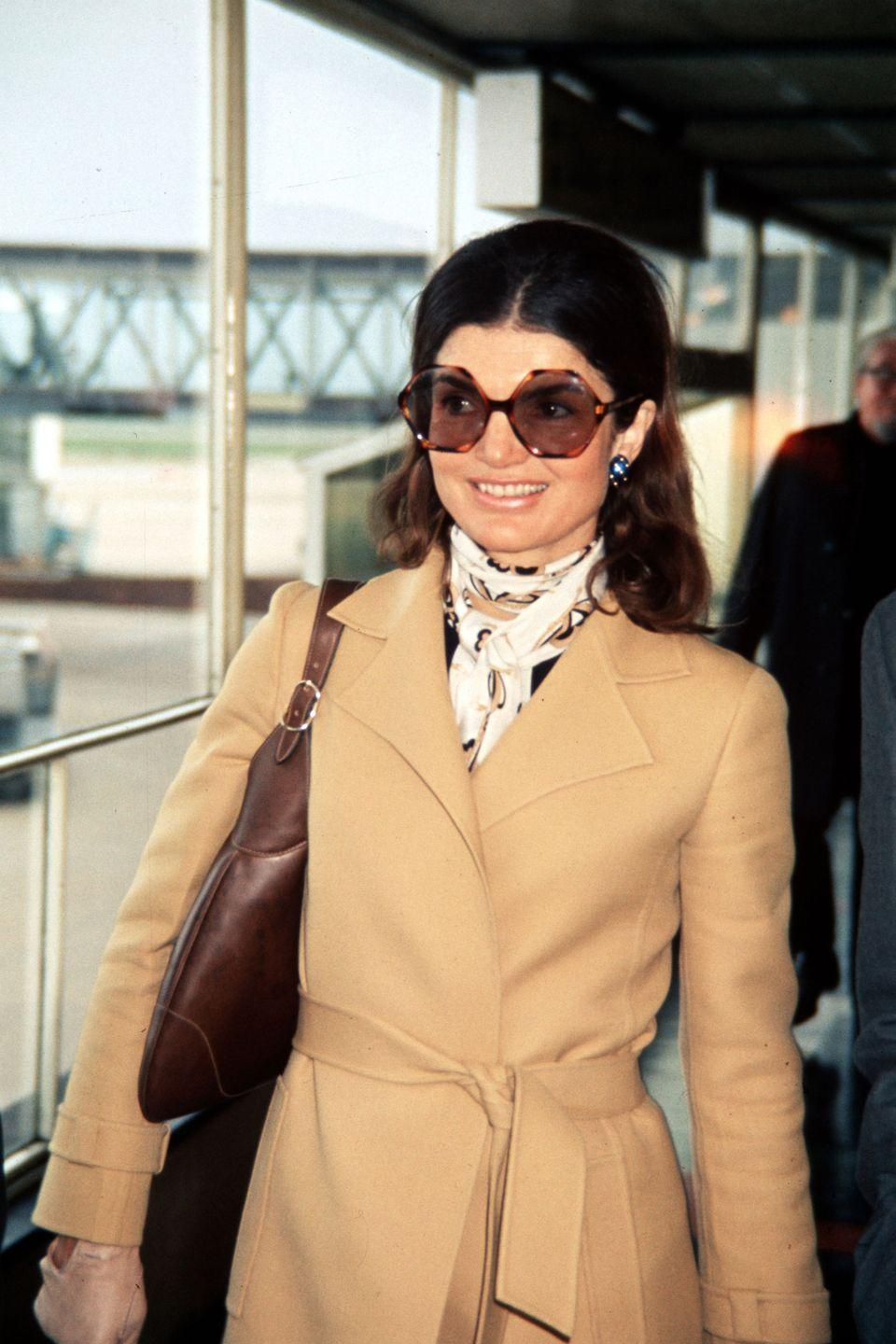 <p>In perfect early 70s style, Jackie pairs a camel coat and large framed sunglasses with a brown leather handbag and insouciant scarf tied around her neck. </p>