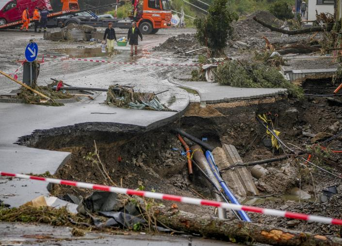 People carry their belongings past a broken road in Schuld, Germany, Friday, July 16, 2021. Two days before the Ahr river went over the banks after strong rain falls causing severals deaths and hundreds of people missing. (AP Photo/Michael Probst)