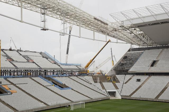 Men work at the still unfinished Itaquerao stadium in Sao Paulo, Brazil, Tuesday, April 15, 2014. The stadium that will host the World Cup opener match between Brazil and Croatia on June 12, will hold nearly 70,000 people in the opener, but after the World Cup its capacity will be reduced to about 45,000. (AP Photo/Andre Penner)