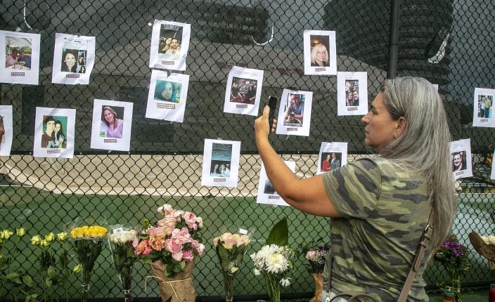 Photos of missing people are posted on a fence near the site of the Champlain Towers South Condo after the building collapsed Friday, June 25, 2021 in Surfside, Fla. The apartment building partially collapsed on Thursday, June 24. (Pedro Portal/Miami Herald via AP)