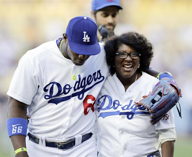 Maritza Valdes Gonzalez, right, is hugged by her son Los Angeles Dodgers' Yasiel Puig after throwing the ceremonial first pitch before the Dodgers' baseball game against the Miami Marlins on Tuesday, May 13, 2014, in Los Angeles. (AP Photo)
