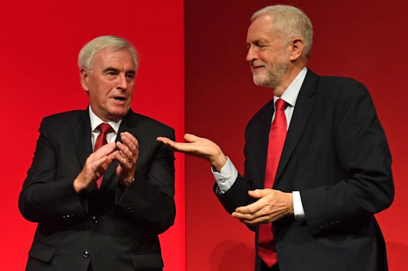 Labour Party Leader Jeremy Corbyn gestures to Mr McDonnell after the latter's speech