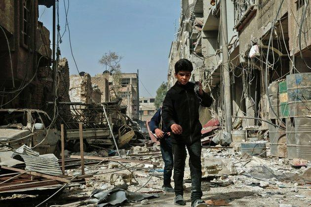 Children walk among the rubble after an airstrike in Douma, in the eastern Ghouta region of Syria, on Monday. The latest strikes killed at least 13 people overnight, the Syrian Observatory for Human Rights said.