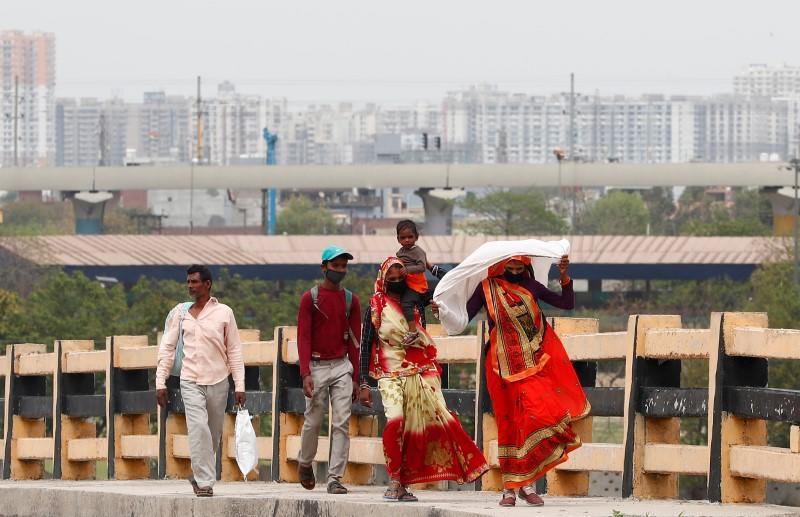 A migrant worker carries her daughter as she walks on a highway with others looking out for a transport to return to their villages, after India ordered a 21-day nationwide lockdown to limit the spreading of coronavirus disease (COVID-19), in Ghaziabad