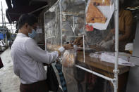 A man wearing a face mask receives take-away food handed over from behind a plastic sheet at a restaurant in Yangon, Myanmar,Monday, Sept. 21, 2020. Myanmar, faced with a rapidly rising number of coronavirus cases and deaths, has imposed the tightest restrictions so far to fight the spread of the disease in Yangon, the country's biggest city and main transportation hub. (AP Photo/Pyae Sone Win)