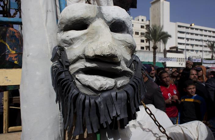 FILE - In this Friday, Feb. 22, 2013 file photo, Egyptians protesters parade with an effigy of a bearded man, mocking Egypt's Islamist rulers, during day six of the general strike, in Port Said, Egypt. For nearly two weeks, protesters and strikers have shut down much of Egypt's Mediterranean city of Port Said, filling the streets with one angry rally after another. Opponents of Egypt's Islamist president are looking to Port Said as a model for stepping up their campaign against him with a possible wave of civil disobedience in other parts of the country. (AP Photo/Nasser Nasser, File)