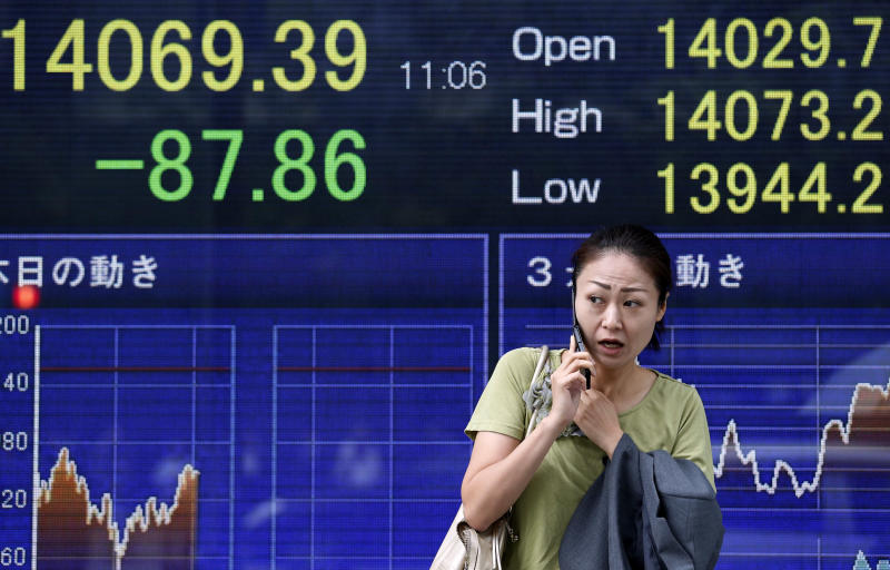 A woman stands in front of an electronic stock board of a securities firm in Tokyo, Friday, Oct. 4, 2013. Uncertainty about how long the partial shutdown of the U.S. government will last kept Asian stock markets on edge Friday. (AP Photo/Koji Sasahara)