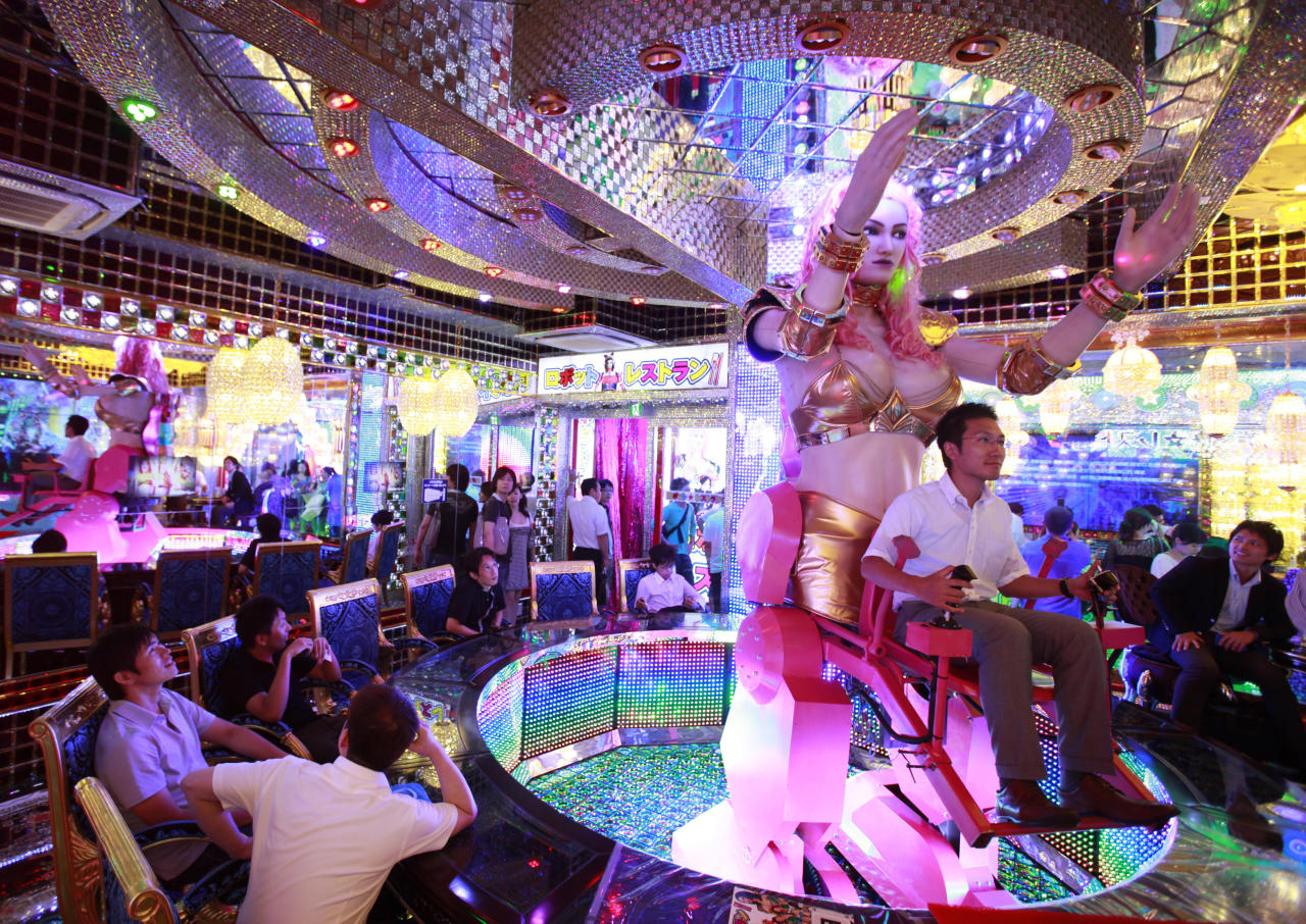 "A customer (R) is seated on a 3.6 metre-high custom-made female robot at the newly opened ""Robot Restaurant"" in Kabukicho, one of Tokyo's best known red light districts, August 16, 2012. It's show time at the ""Robot Restaurant"" a new and high-tech take on the city's decades-old cabaret scene that puts a friendly, if unusual, face on the robot technology in which Japan is a world leader. Picture taken August 16, 2012. REUTERS/Yuriko Nakao (JAPAN - Tags: SOCIETY ENTERTAINMENT FOOD TPX IMAGES OF THE DAY)"