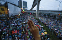 A pro-democracy protesters flashes a three-fingered salute during a protest in Bangkok, Thailand, Saturday, Oct. 17, 2020. The authorities in Bangkok shut down mass transit systems and set up roadblocks Saturday as Thailand capital faced a fourth straight day of determined anti-government protests. (AP Photo/Sakchai Lalit)