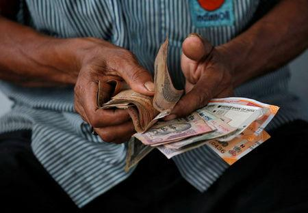 FILE PHOTO:  An attendant at a fuel station arranges Indian rupee notes in Kolkata