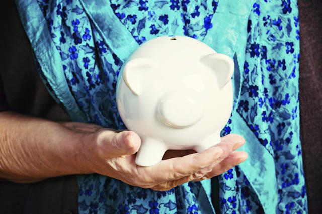 Wrinkled female hand carefully holds a white piggy bank. Symbolic of pensions and senior poverty