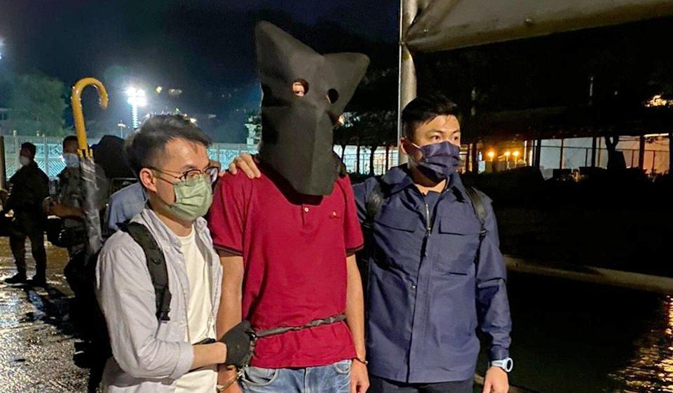 Police officers with the suspect in custody. Photo: SCMP