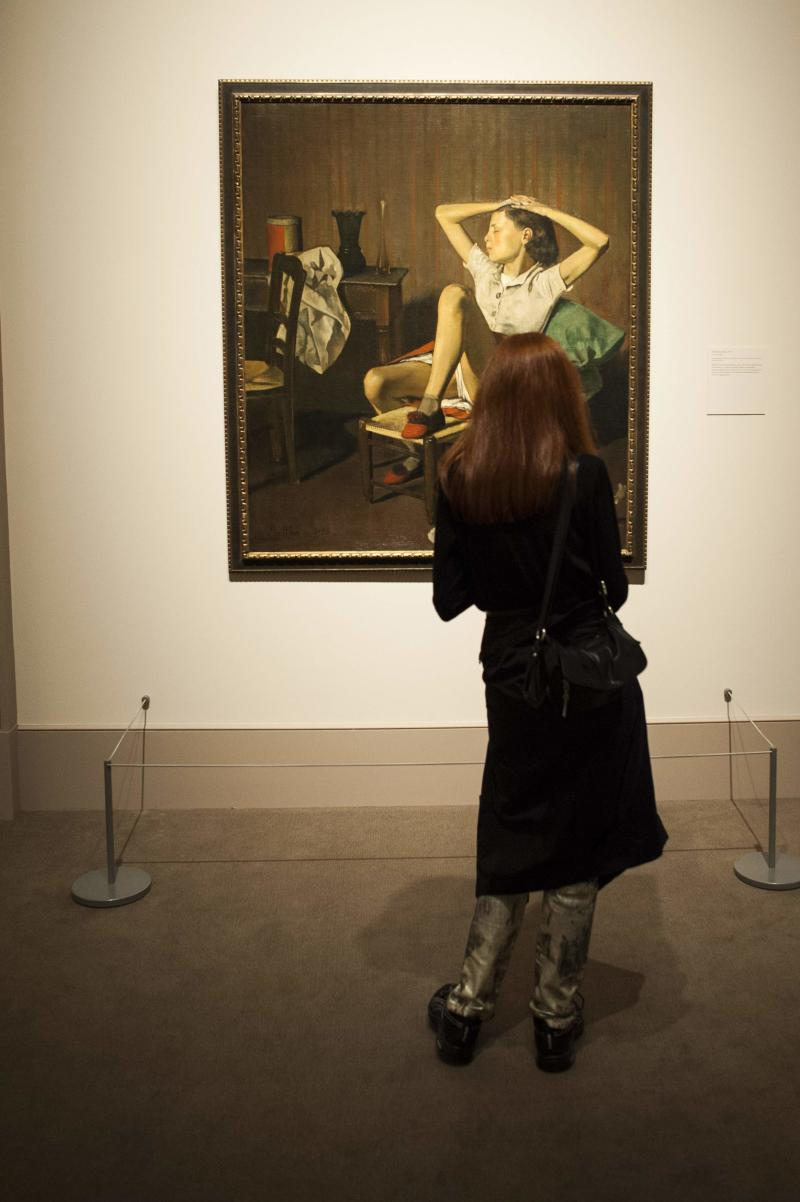 """A woman looks at the painting entitled """"Therese Dreaming"""" by French artist Balthus at the Metropolitan Museum of Art's """"Balthus: Cats and Girls Paintings and Provocations"""" exhibition in New York"""