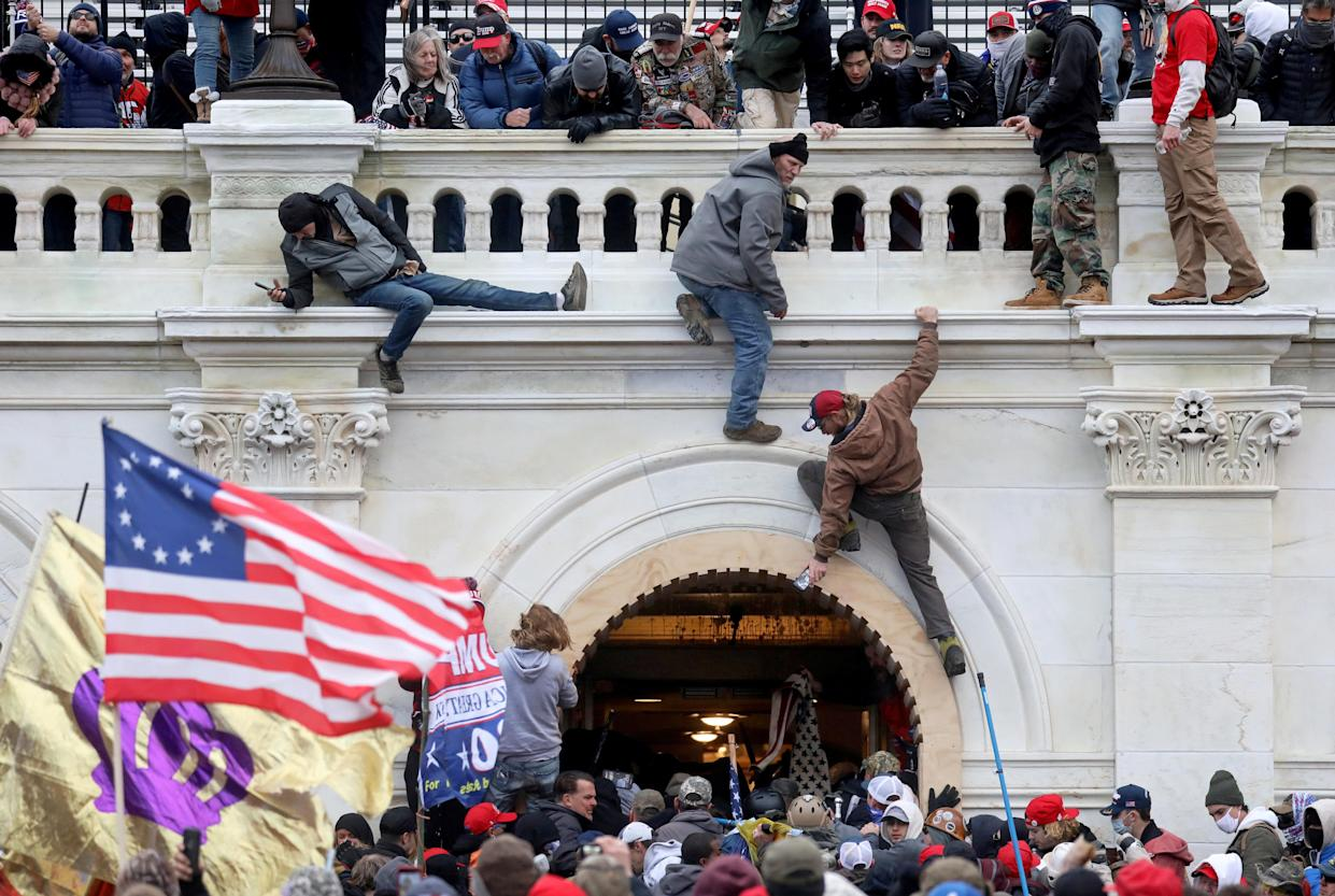 A mob of supporters of former U.S. President Donald Trump fight with members of law enforcement at a door they broke open as they storm the U.S. Capitol Building in Washington, U.S., January 6, 2021. (Leah Millis/File Photo via Reuters)