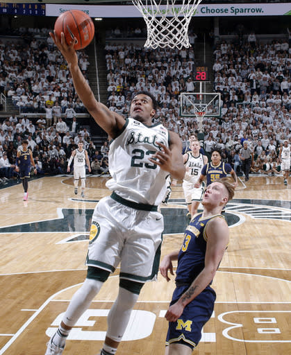 Michigan State's Xavier Tillman, left, puts up a layup against Michigan's Ignas Brazdeikis during the first half of an NCAA college basketball game Saturday, March 9, 2019, in East Lansing, Mich. (AP Photo/Al Goldis)