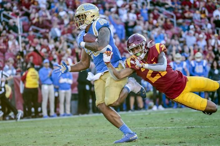LOS ANGELES, CA, SATURDAY, NOVEMBER 23, 2019 - UCLA Bruins tight end Devin Asiasi (86) runs past USC Trojans safety Isaiah Pola-Mao (21) for a third quarter touchdown at the Coliseum. (Robert Gauthier/Los Angeles Times)