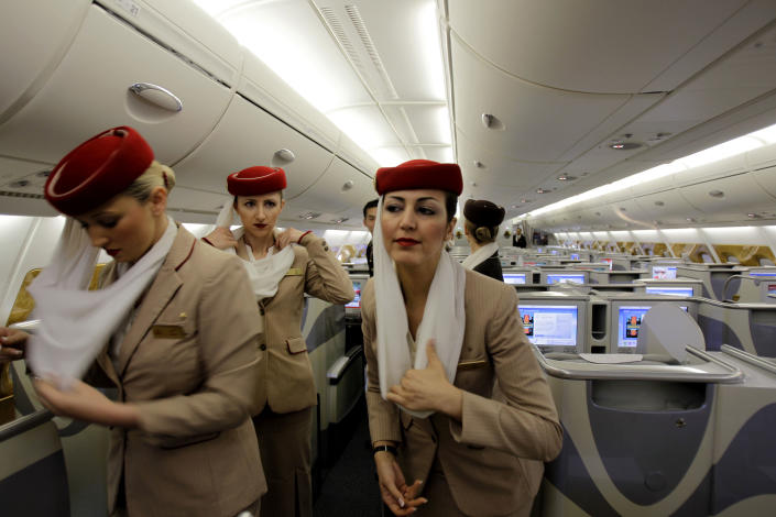 In this Sunday, Feb. 10, 2013, photo emirates cabin attendants prepare the inside an Airbus A380 aircraft for a flight at the new Concourse A of Dubai airport in Dubai, United Arab Emirates. For generations, international fliers have stopped over in London, Paris and Amsterdam. Now, they increasingly switch planes in Dubai, Doha and Abu Dhabi, making this region the new crossroads of global travel. The switch is driven by both the airports and airlines, all backed by governments that see aviation as the way to make their countries bigger players in the global economy. (AP Photo/Kamran Jebreili))