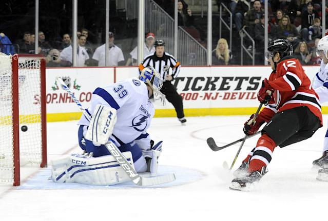 New Jersey Devils' Damien Brunner, right, of Switzerland, scores a goal past Tampa Bay Lightning goaltender Anders Lindback, of Sweden, during the second period of an NHL hockey game Saturday, Dec. 14, 2013, in Newark, N.J. (AP Photo/Bill Kostroun)