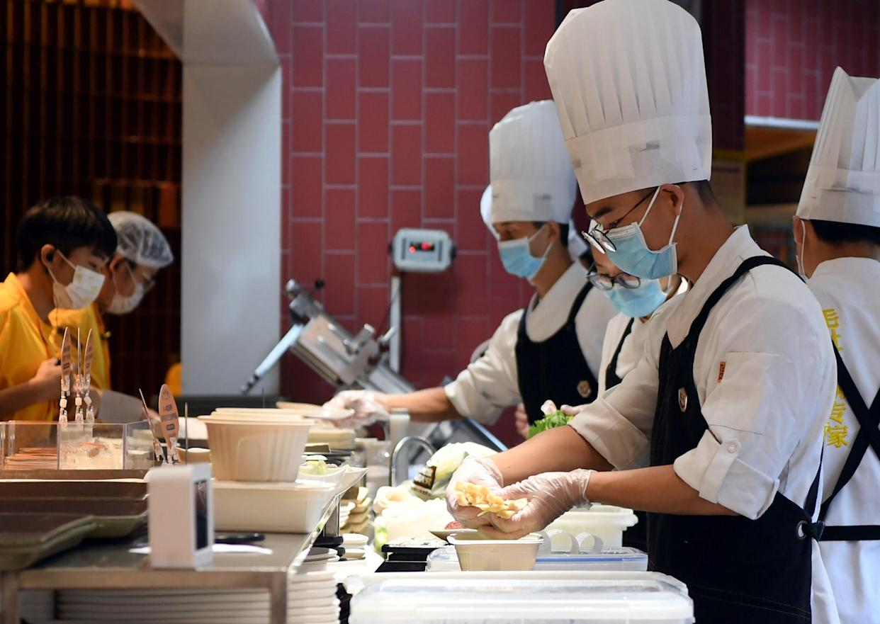 Staff members prepare meals for the customers at a restaurant in Zhengzhou, central China's Henan Province, Aug. 29, 2021. Zhengzhou started on Saturday to allow restaurants to resume dine-in service, while requiring them to conduct regular disinfection, shorten dining hours and provide serving chopsticks and spoons.   Customers and takeaway deliverymen are requested to undergo temperature and health codes scanning before entering restaurants.    Zhengzhou city cleared all its medium- and high-risk areas for COVID-19 on Saturday, with closed-management measures in affected areas lifted, reported the city authorities. (Photo by Li Jianan/Xinhua via Getty Images)