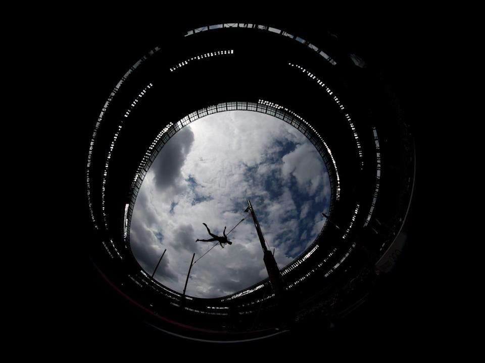 An upward view shows a pole vaulter with the sky in the background at the Olympics