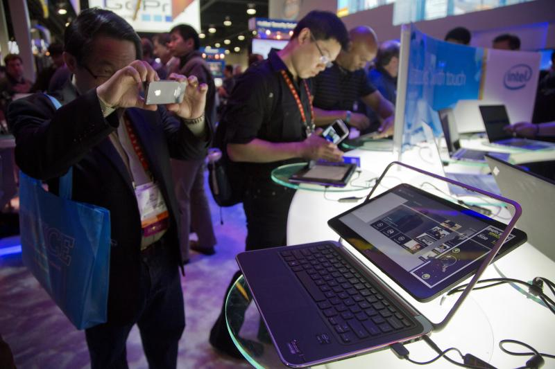 FILE -  In this Tuesday, Jan. 8, 2013,  file photo, an electronics industry affiliate photographs Dell's XPS Ultrabook convertible at the Consumer Electronics Show, in Las Vegas. Dell Inc.'s net income fell 31 percent in the latest quarter as the company continued to be hurt by a shrinking PC market. (AP Photo/Julie Jacobson)
