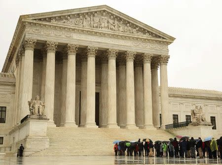 People line up in the rain outside of the US Supreme Court in Washington