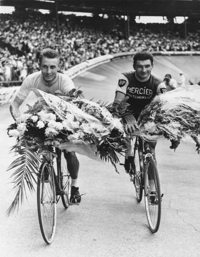 """FILE - This July 14, 1964 file picture shows French cycling ace Jacques Anquetil, left, winning for the fifth time the Tour de France, as he rides an honor round with the Tour's second, Raymond Poulidor, at the Parc des Princes stadium in Paris, France. Tour de France organizers have confirmed that former rider Raymond Poulidor, known as """"the eternal runner-up"""" behind five-time winners Jacques Anquetil and Eddy Merckx, has died. He was 83 years old. (AP Photo, File)"""