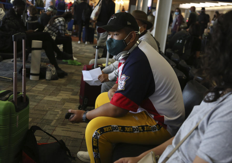 Jalue Dorje waits to board a plane bound for New York to visit family on Wednesday, July 21, 2021, at the Minneapolis−Saint Paul International Airport in Minneapolis. (AP Photo/Jessie Wardarski)